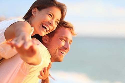 Beach couple laughing in love romance on travel honeymoon vacati